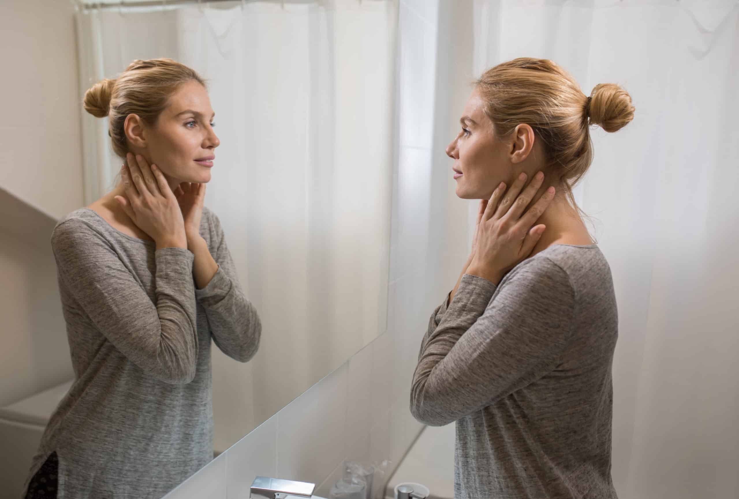 Cosmetic surgery - woman looking in the mirror